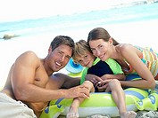 Two generation family sitting on green inflatable toy on beach, smiling, portrait tilt