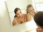 Teenage girls 15-17 looking at reflection in mirror, applying make-up, smiling, rear view tilt