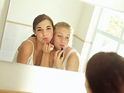 Teenage girls 15-17 looking at reflection in mirror, applying lipstick, pouting, rear view tilt