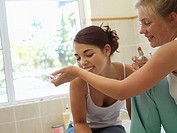 Teenage girl 15-17 smelling perfume on friend's wrist in bathroom, smiling tilt