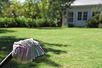 Pair of gardening gloves, garden lawn in background, focus on foreground