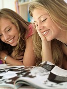 Two teenage girls 15-17 lying on bed, reading magazine, smiling, close-up (thumbnail)