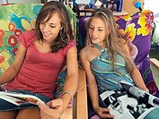 Two teenage girls 15-17 reading magazines in chairs, listening to MP3 player, sharing headphones