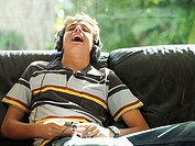 Teenage boy 15-17 relaxing on sofa, wearing headphones, listening to MP3 player, laughing