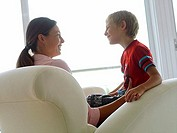 Mother and son 5-7 sitting in chair at home, smiling, face to face, boy in mother's lap, profile