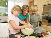 Mother and children 5-8 making cake mix in kitchen, smiling, girl stirring with wooden spoon
