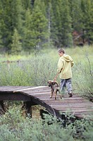 Boy 10-11 with dog on leash walking on boardwalk