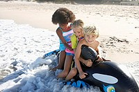Three children 5-10 sitting on inflatable toy whale on beach, playing in surf, smiling