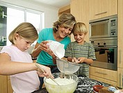 Family making cake mix in kitchen, mother pouring flour, boy 5-7 with sieve, girl 6-8 stirring