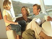 Two generation family relaxing in armchair beside balcony sliding doors, smiling tilt