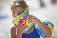 Girl 5-7 blowing air into inflatable water wings on beach, close-up tilt