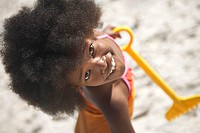 Girl 8-10 standing on beach with yellow toy spade, smiling, portrait, overhead view