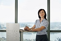 England, London, Canary Wharf, businesswoman standing behind lectern, giving presentation