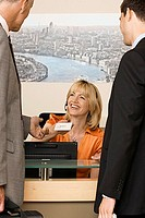 Receptionist working behind reception desk, receiving business card from businessman, smiling
