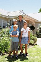 Grandparents standing with grandchildren 6-11 beside flowerbed in front garden, smiling, portrait