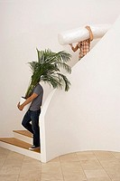 Couple moving house, man carrying large pot plant down staircase, woman carrying dust sheet