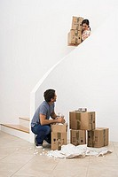 Couple moving house, woman carrying boxes down staircase, man crouching at bottom, side view