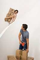 Couple moving house, woman carrying boxes down staircase, man sealing box with duct tape