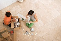 Couple moving house, packing boxes with crockery wrapped in paper, kneeling on floor, overhead view
