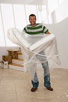 Man moving house, carrying white chair wrapped in plastic sheet in sparse room, smiling, portrait