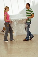 Couple moving house, carrying white chair wrapped in plastic sheet in room, smiling, side view