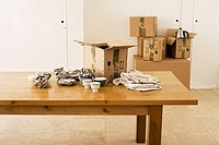 Crockery wrapped in paper beside cardboard box on dining room table, sealed boxes in background