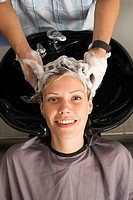Hairdresser shampooing woman´s hair in salon, smiling, front view, portrait, elevated view