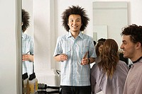 Customers sitting in hair salon, focus on hairdresser holding comb and scissors, smiling portrait