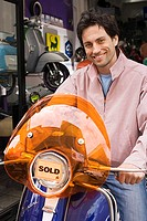 Man standing outside shop with new scooter, orange sold sticker on headlight, smiling, portrait