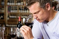 Man smelling glass of red wine in off-licence, side view, close-up, focus on foreground