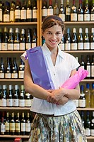 Woman standing with bottles of wine wrapped in tissue paper in off-licence, smiling, portrait