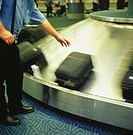 Man taking suitcase from luggage carousel at airport, blurred motion, low section
