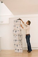 Businessman standing beside tall stack of file boxes in empty office, opening lid of top box