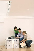 Three new business partners working in empty office, using laptop on file box, side view