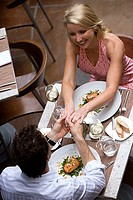 Couple dining in restaurant, holding hands, elevated view