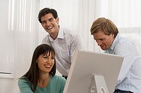 Three business colleagues working at desk in office, woman using computer, smiling