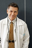 Male dentist standing in dental surgery, smiling, front view, close-up, portrait