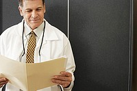 Male dentist standing in dental surgery, holding medical file, smiling, front view