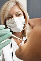 Female dentist wearing surgical mask, examining patient, using angled mirror, close-up