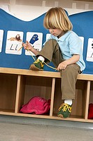 Blonde boy 4-6 sitting on bench in classroom, tying shoelace, alphabet cards on wall tilt
