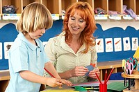 Boy 4-6 making card at desk in classroom, teacher assisting, smiling
