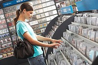 Young woman sifting through CDs in record shop, side view tilt