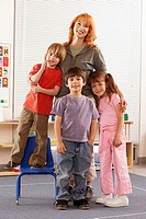 Teacher and children 4-6 standing in classroom, smiling, portrait