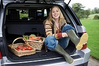 Woman sitting beside baskets of fresh vegetables in car boot, putting on wellington boots, smiling