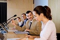 Business colleagues sitting in conference room in front of visual screens and microphones, side view