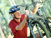 Active senior man in cycling helmet checking bicycle, close-up tilt