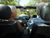 Senior couple driving in convertible car along country road, smiling, rear view