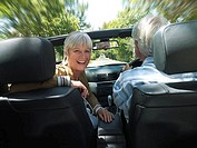 Senior couple driving in convertible car along country road, woman smiling, rear view