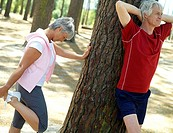 Active senior couple in sportswear warming up, woman stretching legs, man with hands behind head