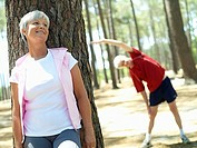 Active senior couple in sportswear warming up, focus on woman leaning against tree, smiling